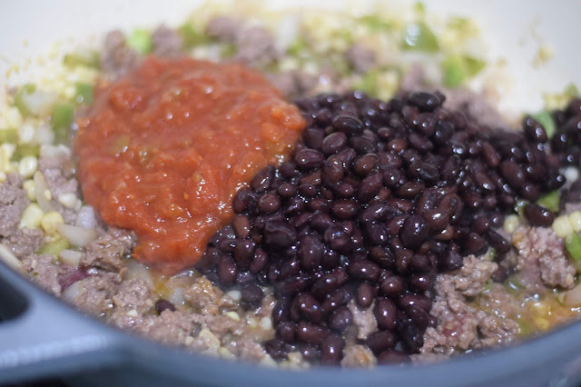 Salsa and black beans being added to the meat mixture.