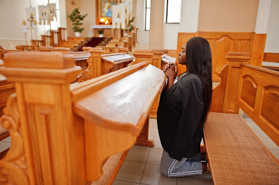 Mom kneeling and praying in church
