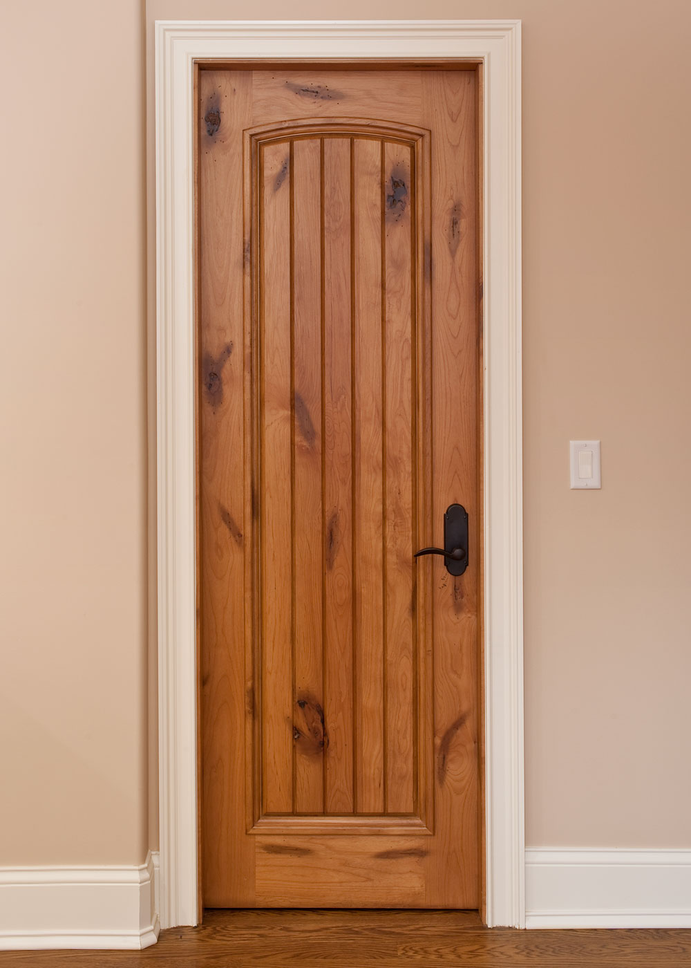 Knotty alder door with white trim and planked detail in center.