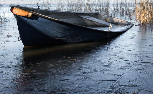 järveen kiinni jäätynyt vene soutuvene keväällä