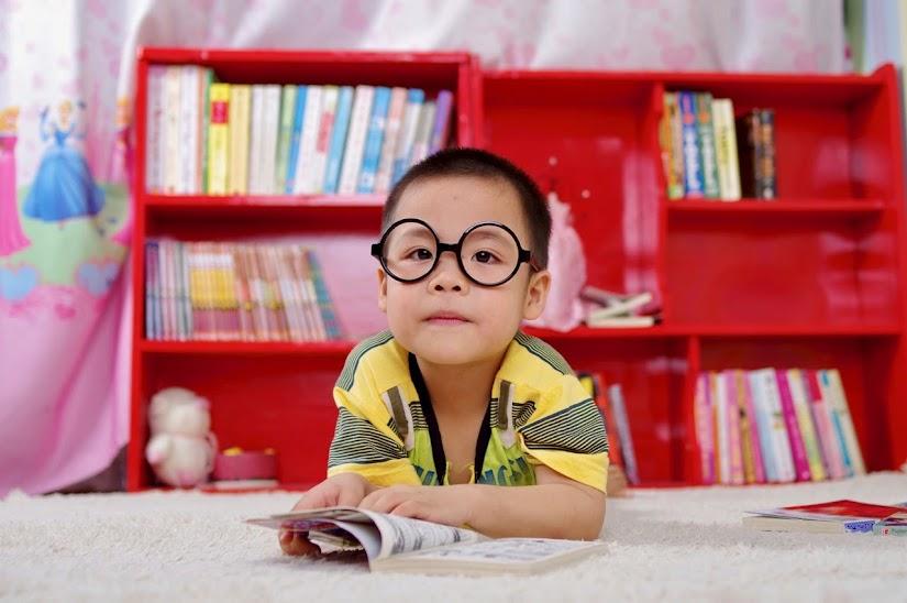 Niño leyendo con gafas