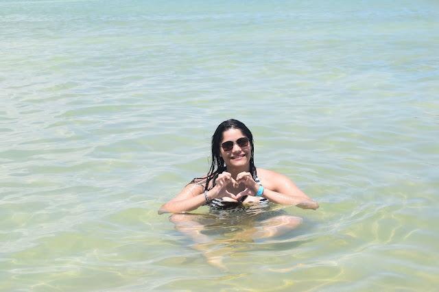 mulher no mar fazendo sinal de coraçao com as maos