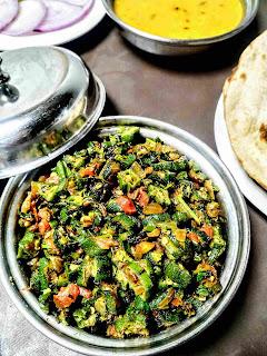 Serving bhindi ki sabji bhindi fry in a bowl with dal and roti