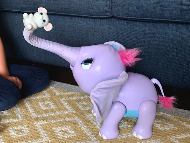 A purple, pink and blue elephant toy with it's trunk in the air holding a toy mouse