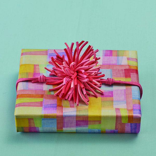 colorfully wrapped, rectangular gift with pink rawhide leather pom pom bow