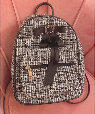 grey round backpack with a black bow from Swankiss