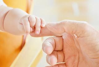 infant grabbing finger