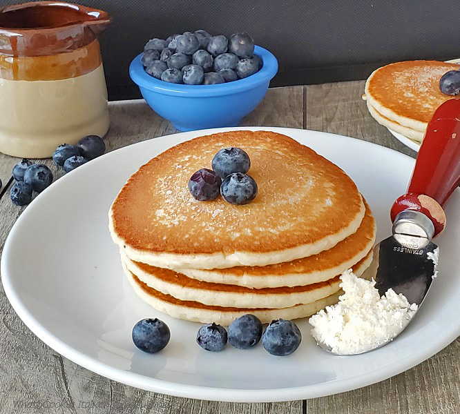 this is a photo of buttermilk pancakes stacked up with blueberries on top. There is a wooden handled butter knife on the white plate with a pitcher of syrup and more pancakes on a plate in the background along with a bowl of blueberries in a small white ceramic bowl