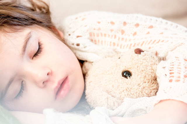 Image: Sleeping with her brown plush bear, by Snapwire on Pexels