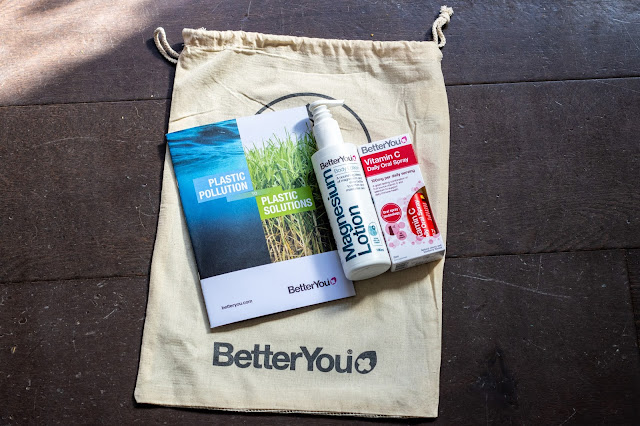 "A fabric bag saying ""BetterYou"" a plastic magnesium lotion and Vitamin C spray next to a booklet called ""Plastic Pollution to Plastic Solution"""