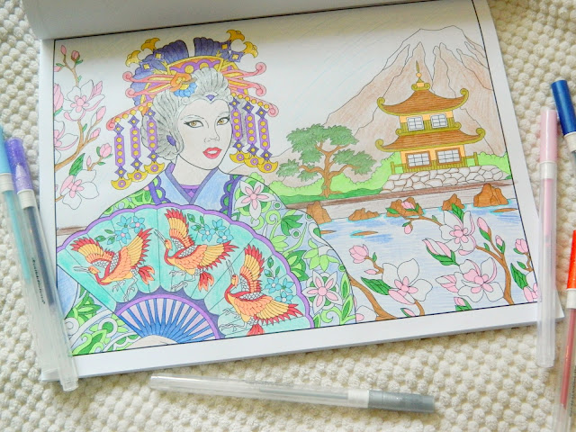 A photo showing a completed colouring book of a Japanese Geisha standing by a pond in a beautiful garden