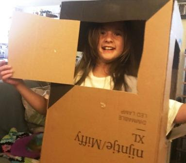 Girl inside Nijntje/Miffy box, with face and arms sticking through box windows