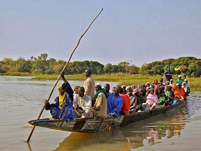 Hommes et femmes débarquent au marché de Boubon en pirogue