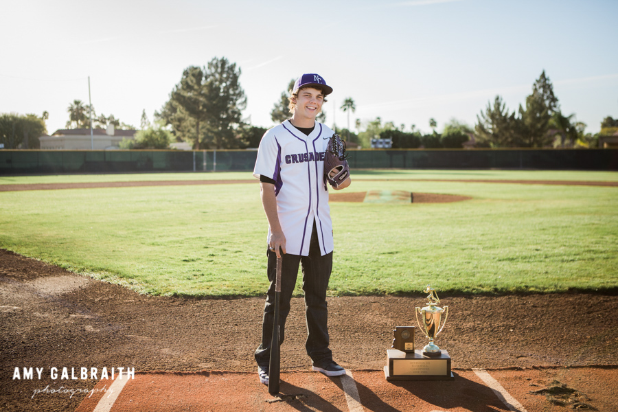 baseball player standing with trophy on home plate