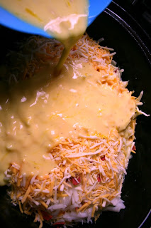 Pouring egg mixture over hash brown, bacon and cheese layers in the slow cooker