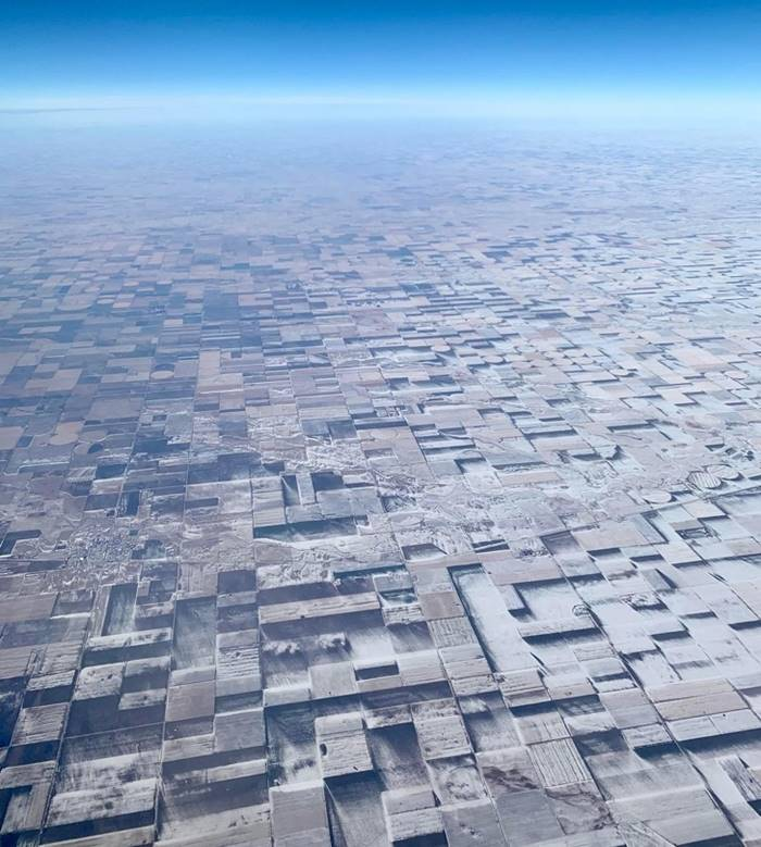 Flat farmland with melted snow creates a three-dimensional illusion.