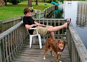 A teen relaxing with his dog near a river bank.