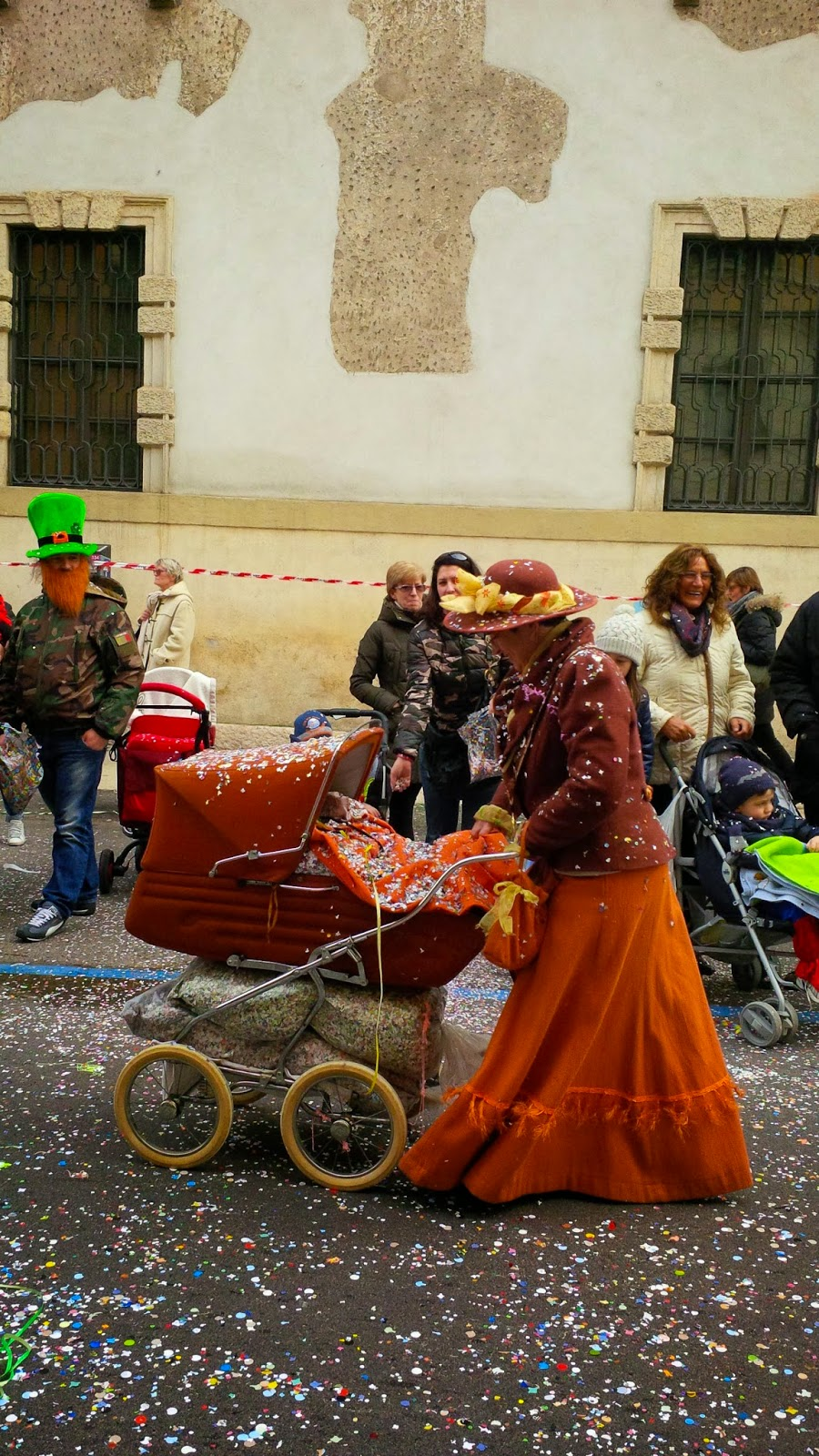A lady in costume pushes a buggy stuffed with large bags filled with confetti at Verona Carnival