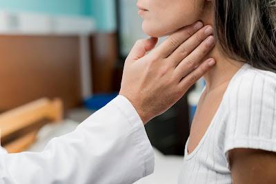 Doctora checando la garganta de su paciente