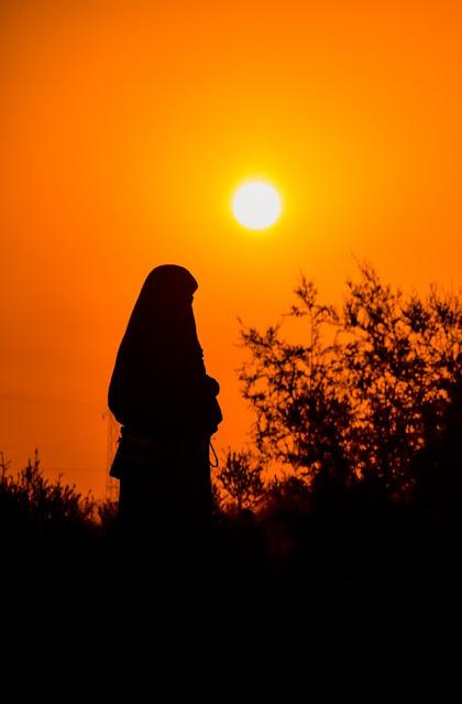 Foto siluet seorang muslimah di kala senja