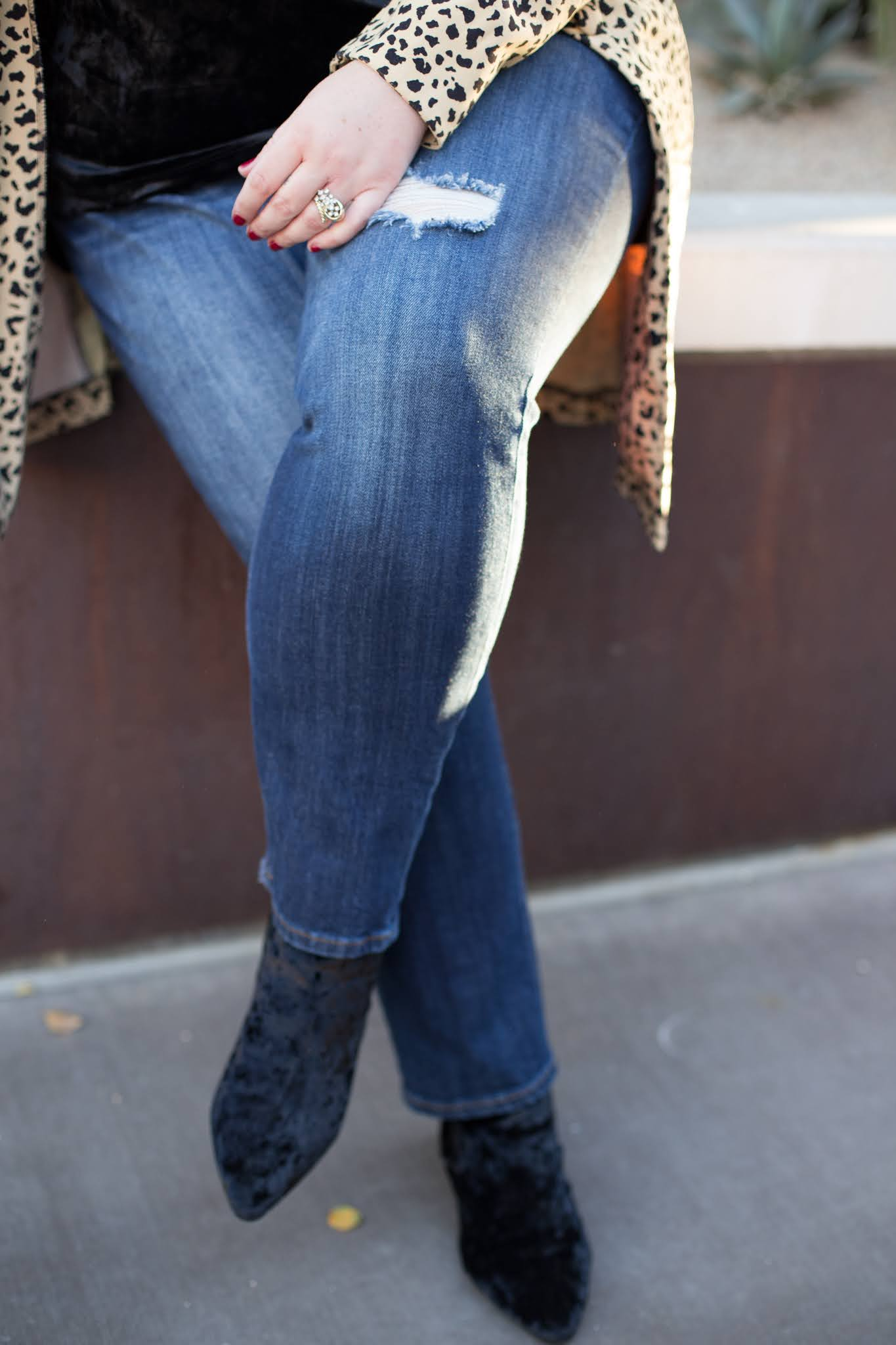 woman wearing black velvet and animal print trench coat and ripped jeans