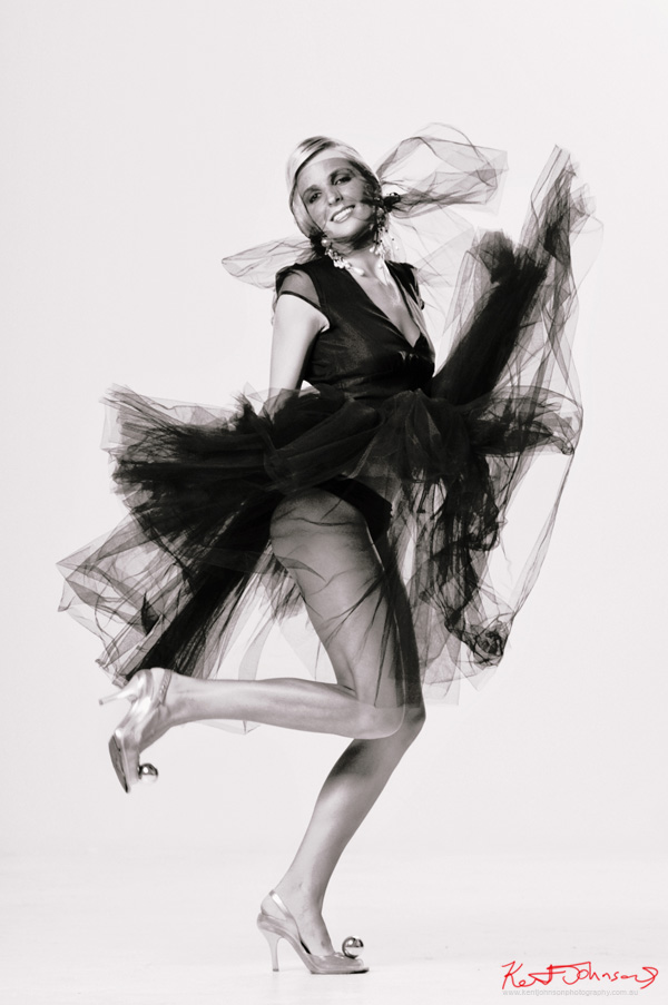 Black tulle dress on white background with, Marilyn Monroe inspired pose. Studio fashion photography by Kent Johnson