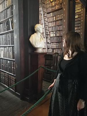 Reta Anna Maria seisoo vanhanaikaisen kirjahyllyn edessä. Kuva on otettu Dublinin Trinity Collegen kirjastossa.