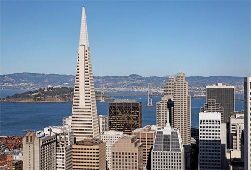 Bonita vista urbana del distrito financiero de la ciudad de San Francisco con la famosa Transamerica Pyramid en primer término y el Puente de la Bahía de San Francisco (Oakland Bay Bridge), al fondo