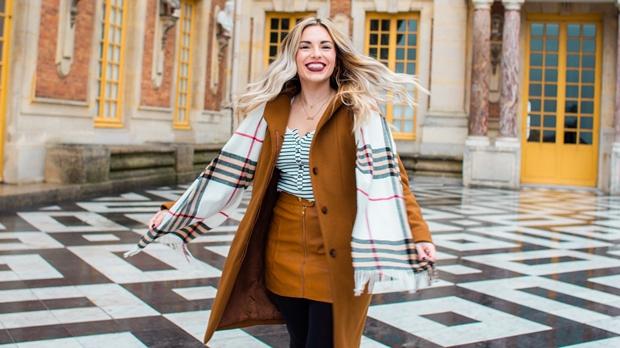 Mulher loira feliz girando o seu corpo com roupas de inverno