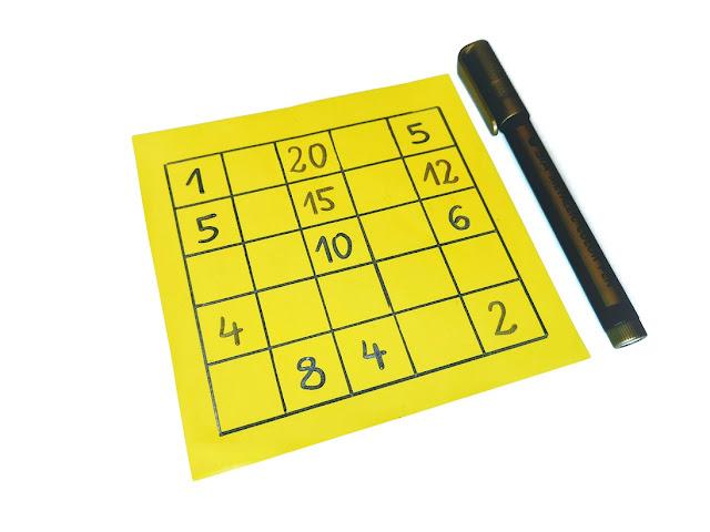 na zdjęciu żółta karta a na niej narysowana tabelka 5x5, w tabelce liczby a obok leży pisak