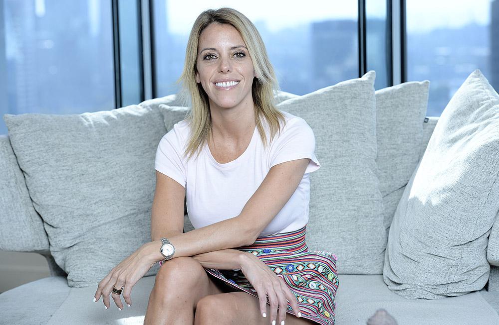 Paula Gray consultora en sustentabilidad sentada en sillón gris