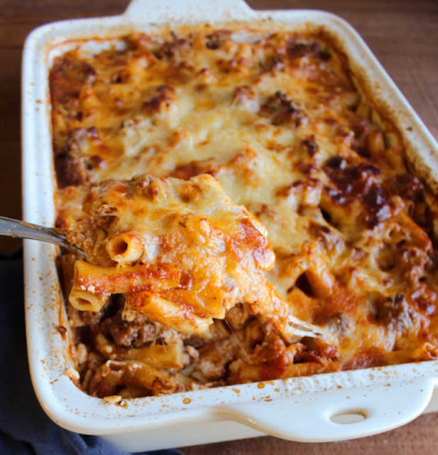 spoon lifting serving of baked ziti out of pan