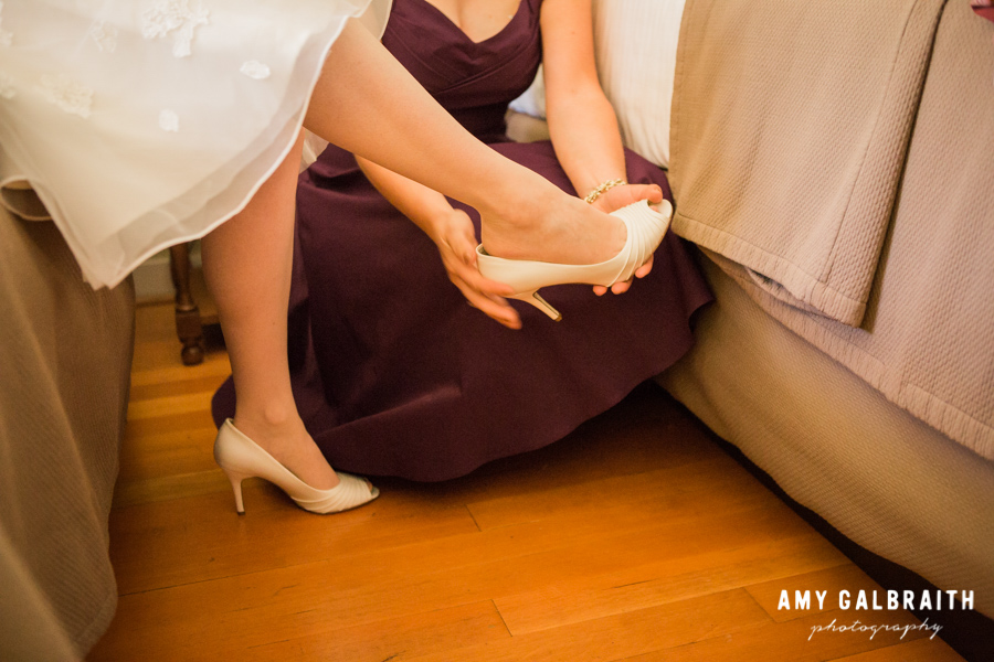 bridesmaid helping bride put wedding shoes on