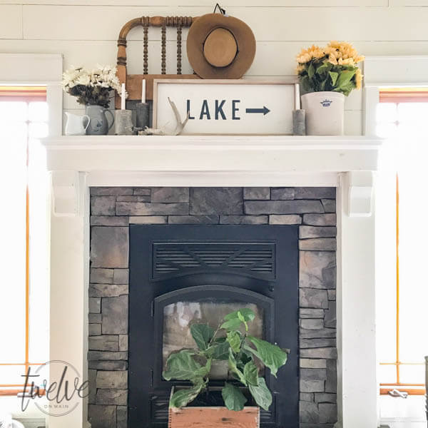 Lighten up stone fireplace with white wood surround