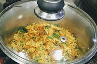 Garnished veg biryani in a covered pot