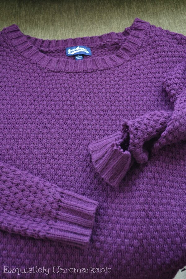 Purple sweater with a hole in the sleeve