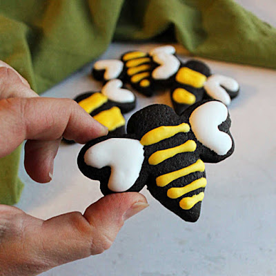 black chocolate bee cookie with yellow icing stripes and white icing wings