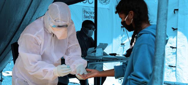 Una trabajadora de salud hace la prueba del COVID-19 a una niña en Nepal.© UNICEF Nepal