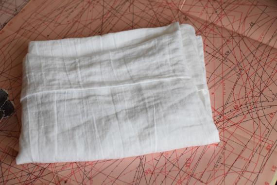 Kuvassa on valkoinen taiteltu taskutyynyliina vaaleanpunaisen kaavapaperin päällä.
