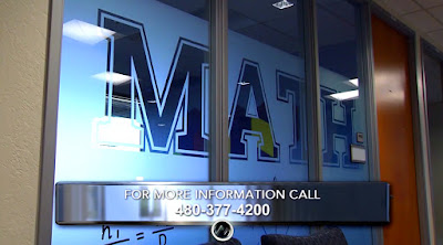 Snapshot from video of Math Emporium decorative window with the word Math along with math symbols etched into panel.  Text: for more information call 480-377-4200
