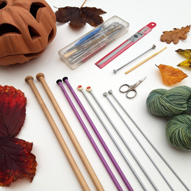 A flatlay of a range of knitting needles in wood, plastic and metal with knitting accessories and a small pair of ornate scissors.  To the top left is a terracotta pumpkin lamp, to the right are two skeins of green yarn and around the edges are autumn leaves