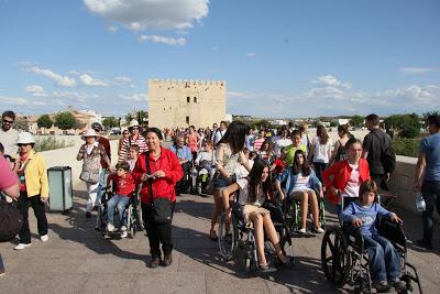Jóvenes y niños se desplazan por el puente romano en silla de ruedas.