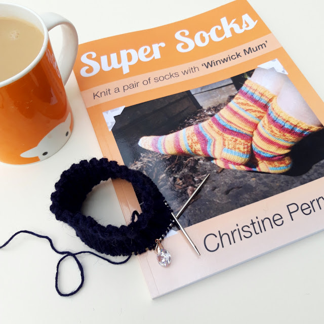 A photo showing an orange copy of Super Socks sock knitting tutorial book next to an orange mug containing tea.  On the book is a navy blue sock cuff on a circular knitting needle.  The background is cream.