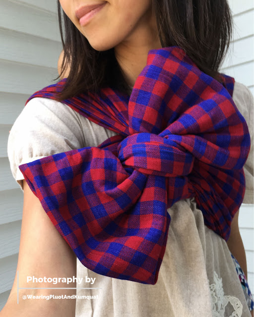 [Image of a tan skin bespectacled woman wearing a barefoot toddler on her back using a red and blue checked woven wrap finished with a large bow on the front. Image is from smiling lips through torso and focused on the large bow.]