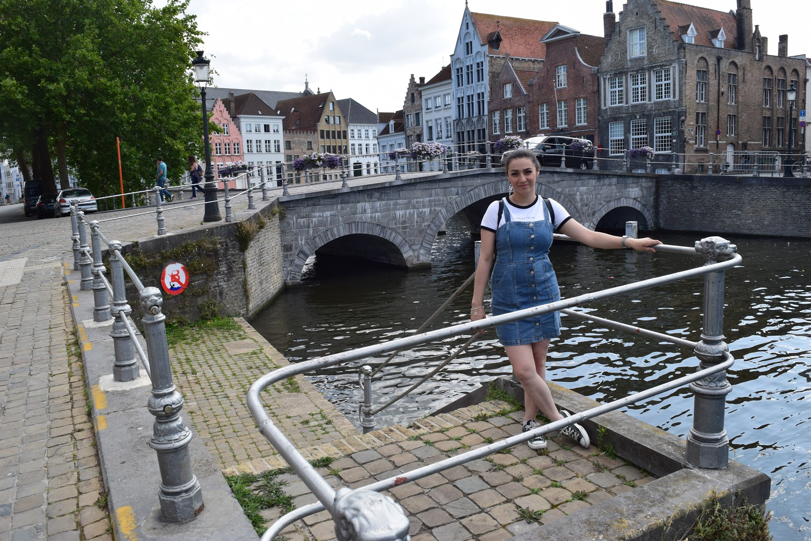 Me standing in front of a canal in Bruges. There is a bridge in the background and houses along the sides. There is a tree on the right and cars driving over the bridge. I am holding the silver banister wearing a blue button down denim dress and a white t-shirt with black edging. I am wearing black converse trainers on my feet.