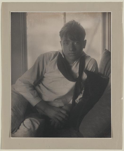 Tony Costanza in sailor suit, seated, leaning on pillows, 1911, F. Holland Day