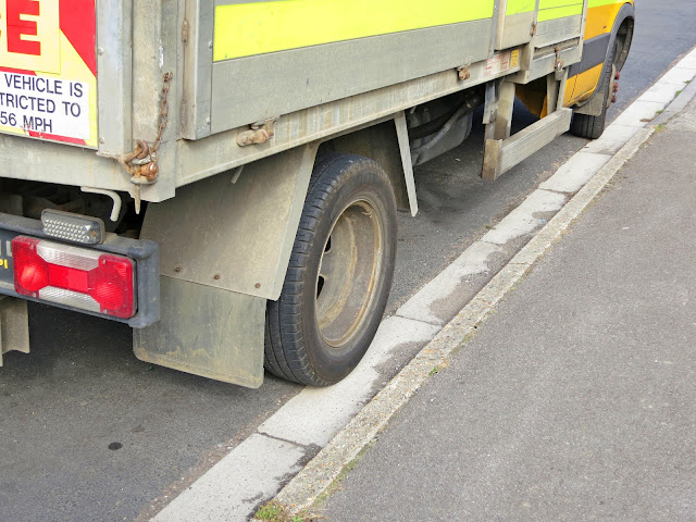 Grey lorry with bright yellow and orange safety flashes