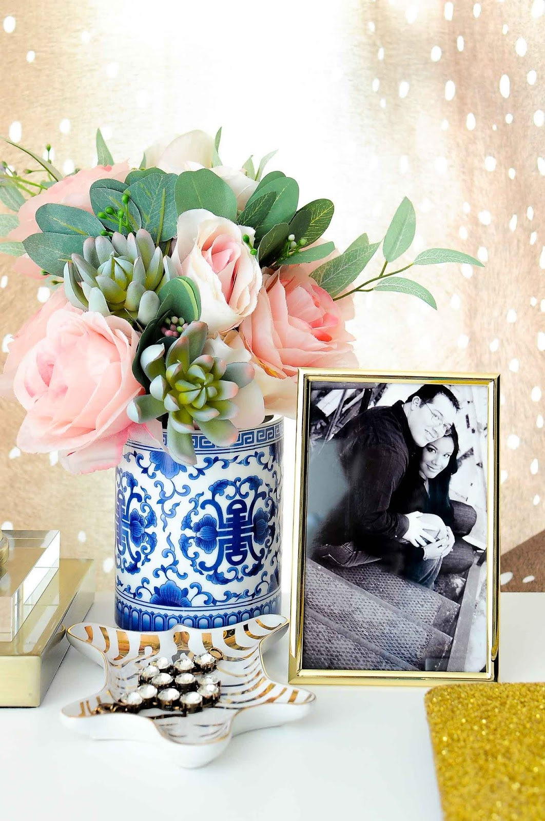 Pink roses and faux succulents in a blue and white ginger jar chinoiserie vase on a white desk in a feminine home office space.