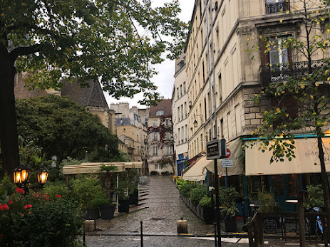 Pebble alley after rain with low rise apartment around in Paris