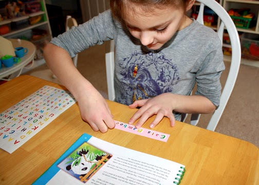 """Tessa spelled out """"Endangered"""" and """"Eats Bamboo"""" with stickers to add to the panda portion of the Team Animal Mural."""